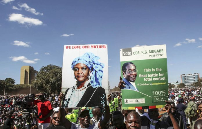 Youths from the ruling Zanu-PF party hold portraits of President Robert Mugabe and his wife Grace during the