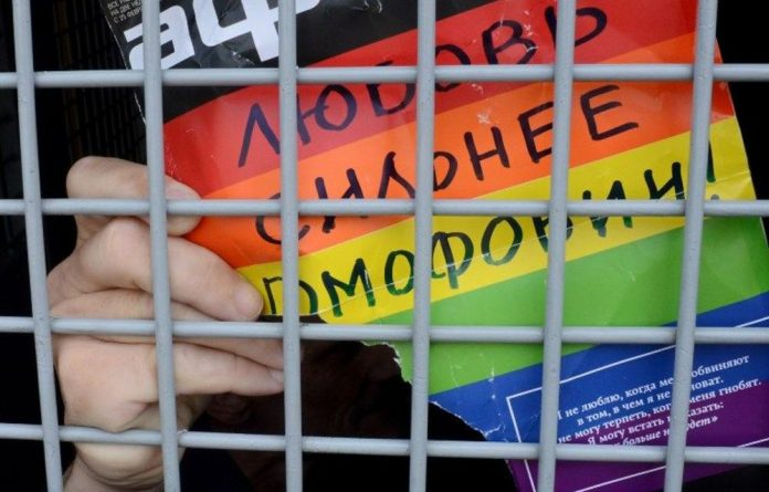 A Russian gay and LGBT rights activist shows a sign reading 'Love is stronger than homophobia' from inside of a Russian riot police van during an unauthorised gay rights activists rally.