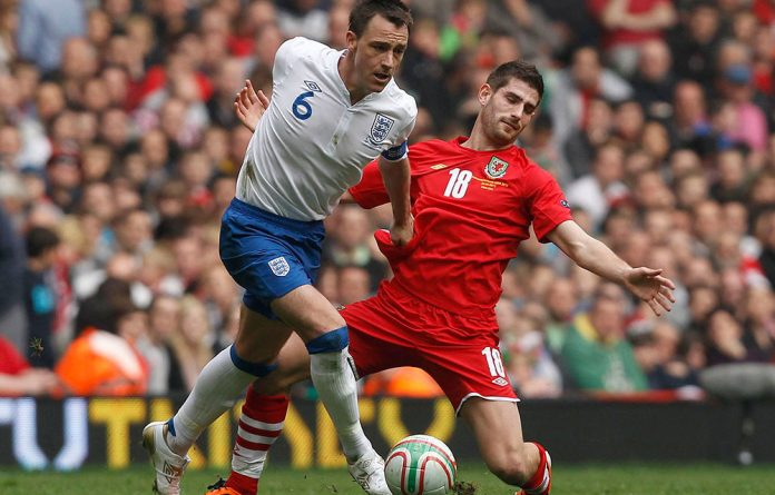 England's John Terry challenges Wales' Ched Evans
