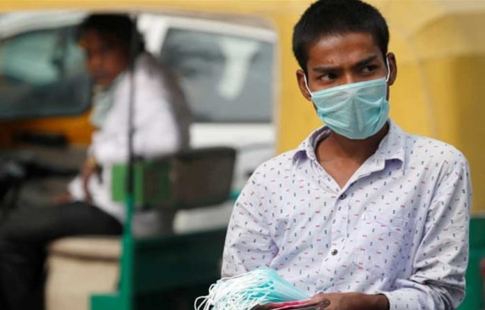 A man sells surgical masks on a smoggy day in New Delhi