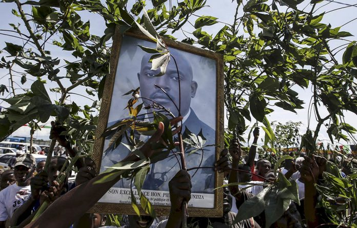Supporters of Burundi's President Pierre Nkurunziza carry his picture as they wait for him to return to the capital of Bujumbura in May last year.