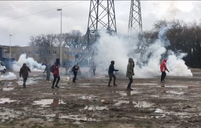 Refugees run and cover their faces after French police fire tear gas in Calais.
