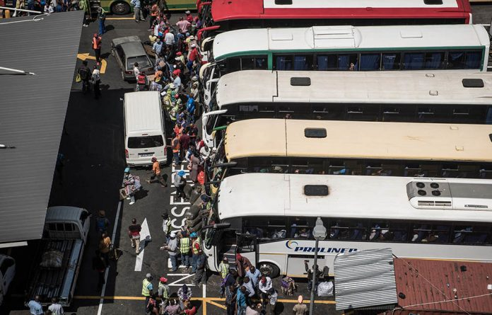 Long-distance buses do a roaring trade as thousands of Zimbabweans who work in South Africa head home for the Easter break.