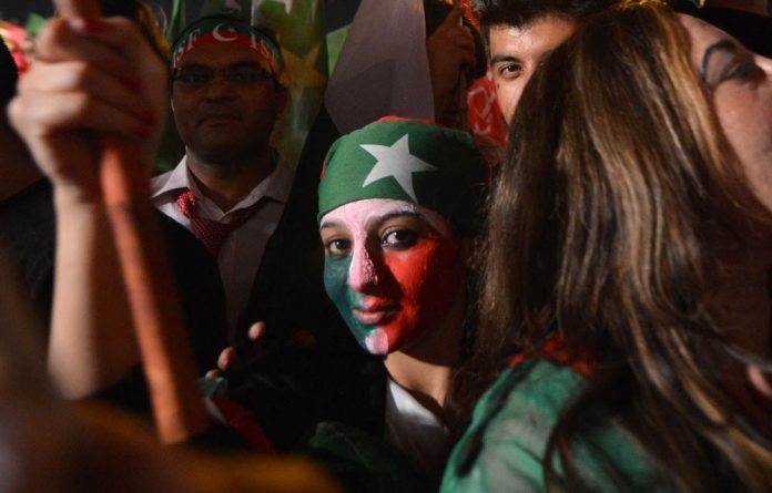 A face painted supporter of Pakistani politician and former cricketer Imran Khan takes part in the last election campaign meeting in Islamabad.