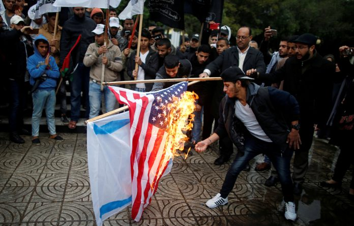 Palestinians burn an Israeli and a US flag during a protest against the US intention to move its embassy to Jerusalem and to recognize the city of Jerusalem as the capital of Israel