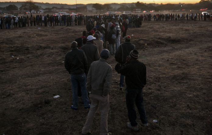 One at a time: Immigrants wait in an open area outside the home affairs offices in Pretoria for days to get permits.