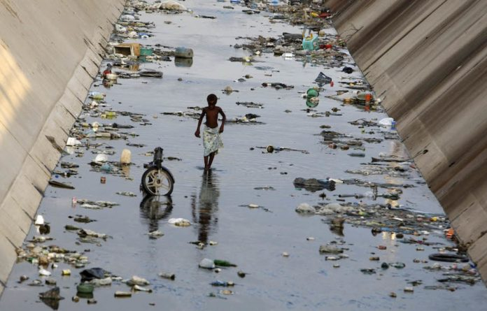 Resource abuse: An Angolan boy walks in a canal in Benguela city. The burden of environmental exploitation by big industry