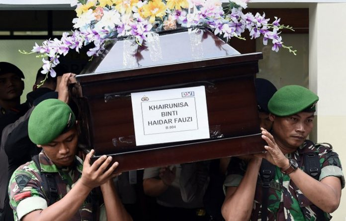 Indonesian military personnel carry the coffin containing the remains of Khairunisa Binti Haidar Fauzi
