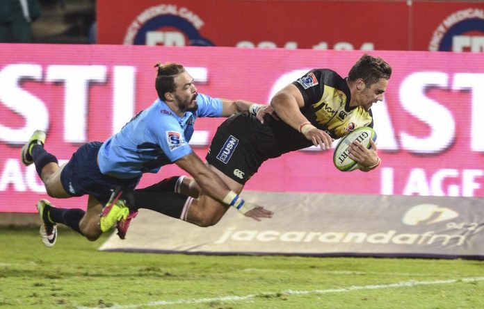 Bjorn Basson of the Bulls can't stop Rohan Janse van Rensburg of the Lions from scoring during the Super Rugby match between the Bulls and Lions this past weekend.