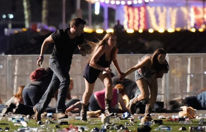 People run from the Route 91 Harvest country music festival after hearing the sound of gunshots.