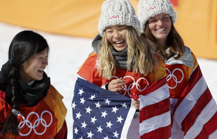 Gold medallist Chloe Kim of the U.S. celebrates while flanked by silver medallist Liu Jiayu of China and bronze medallist Arielle Gold of the U.S. during the flowers ceremony.
