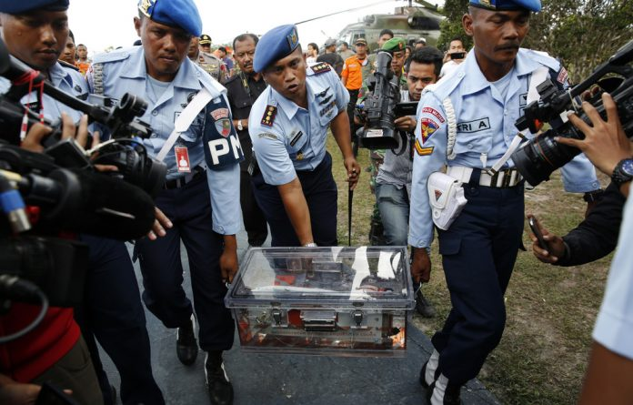 Military policemen carry the flight data recorder of AirAsia QZ8501 at the airbase in Pangkalan Bun