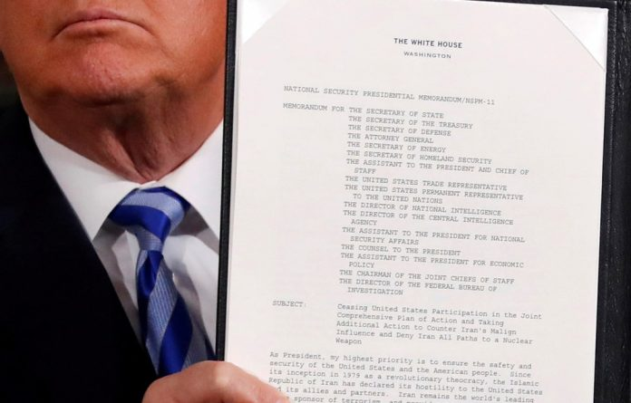 US President Donald Trump holds up a proclamation declaring his intention to withdraw from the JCPOA Iran nuclear agreement after signing it in the Diplomatic Room at the White House in Washington