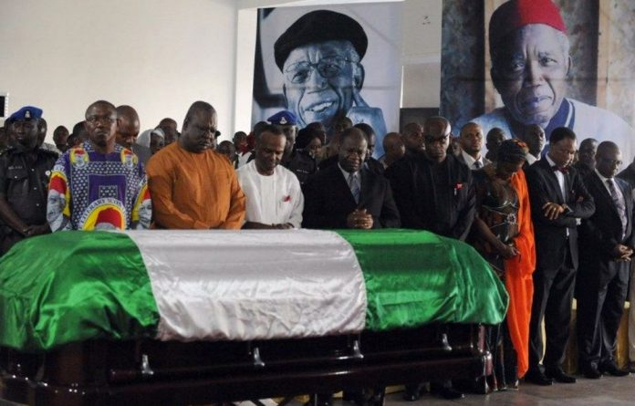 Mourners pray in front of the coffin bearing the body of late Nigerian writer Chinua Achebe upon arrival at Abuja airport.