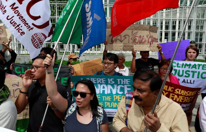 Environmental activists protest in front of the United Nations Conference Centre in Bangkok
