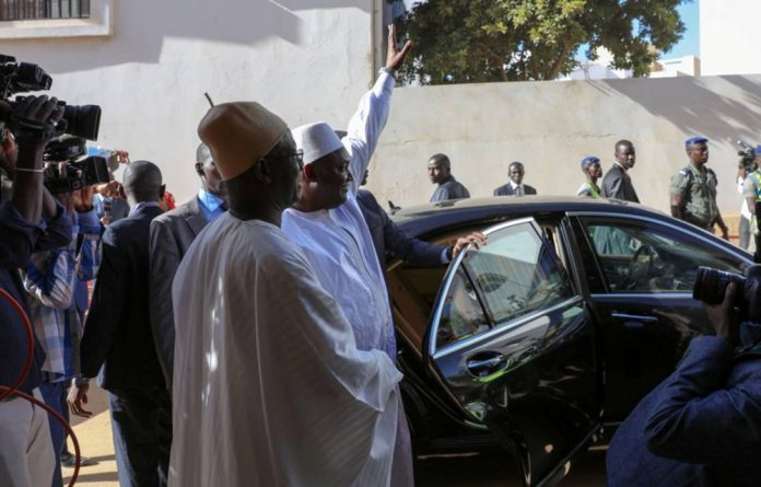 Gambia President Adama Barrow waves to well-wishers after his inauguration ceremony at the Gambian embassy in Dakar