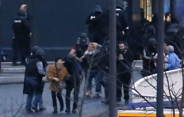Members of the French police special forces evacuate the hostages after launching the assault at a kosher grocery store in Porte de Vincennes