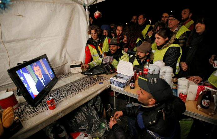 Protesters wearing yellow vests watch French President Emmanuel Macron on a TV screen at the motorway toll booth in La Ciotat