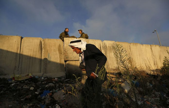 Israeli soldiers sit near part of Israel's controversial barrier as a Palestinian walks towards Qalandiya checkpoint near the West Bank city of Ramallah.