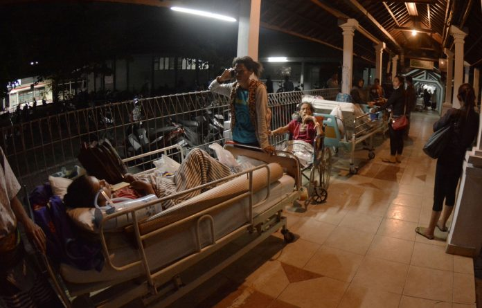 Hospital patients are moved outside after a large earthquake struck on the nearby island of Lombok