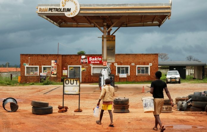 Children walk past a petrol station closed after protests in Harare