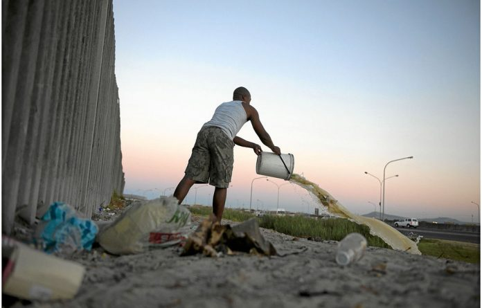 Residents of Khayelitsha clear buckets used as toilets during the night.