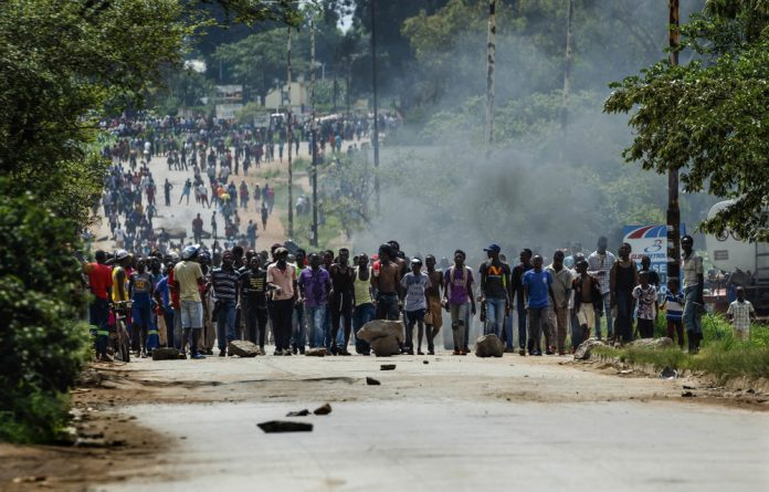 Angry protesters barricade the main route to Zimbabwe's capital Harare from Epworth township after the government announced a huge hike in fuel prices.