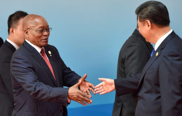 Chinese President Xi Jinping and President Jacob Zuma shake hands before the group photo session of Dialogue of Emerging Market and Developing Countries