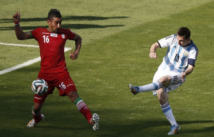Lionel Messi shoots past Iran's Reza Ghoochannejhad to score during the Group F match between Argentina and Iran in Belo Horizonte.