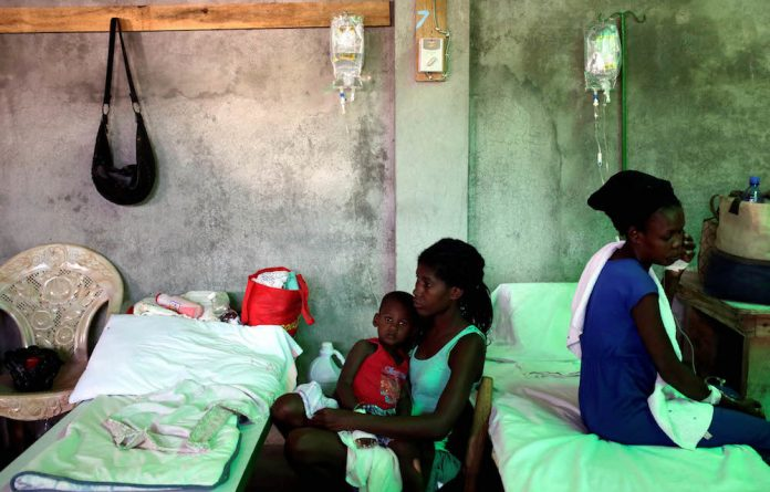 A woman takes care of her son who is receiving treatment for cholera in Haiti.