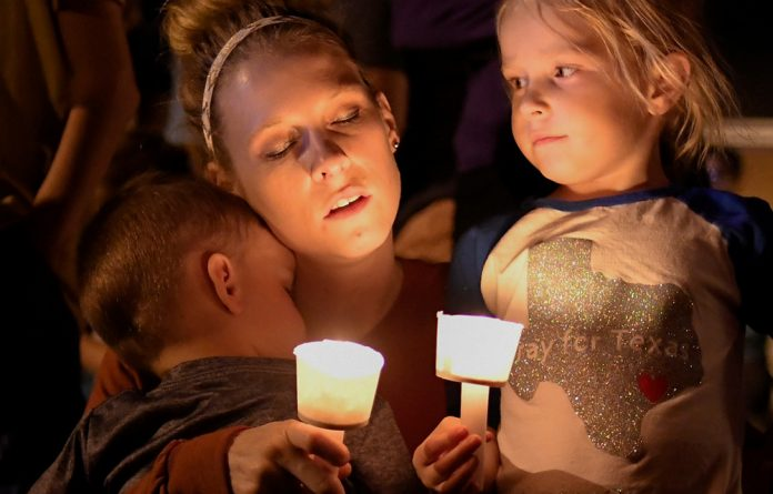 A woman and her children take part in a vigil for victims of a mass shooting in Sutherland Springs
