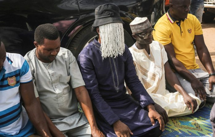 Ghanaian Investigative journalist Anas Aremeyaw Anas prays alongside colleagues and friends for slain investigative journalist Ahmed Husein Suale on January 18 2019.