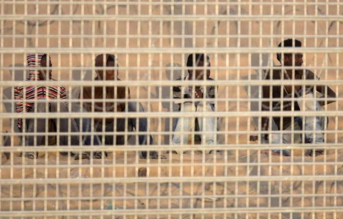 A group of African migrants seen on September 6 2012 behind the border fence after being trapped for seven days between fences on the Israel-Egyptian border.