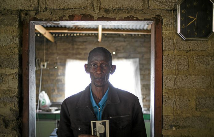 George Mphela holds a photograph of his father