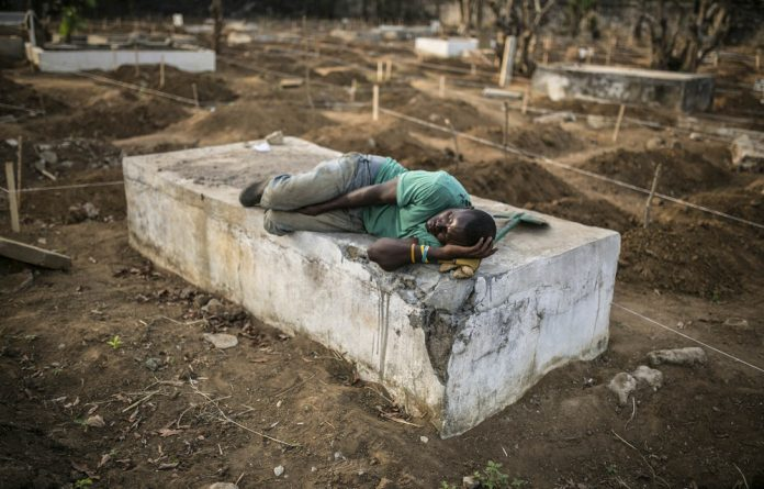 Deadly business:  A grave digger sleeps near the graves of Ebola victims in Freetown