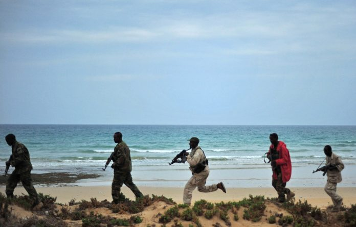 Sensitive: Security forces patrol a section of Somalia's coastline. Critics oppose moves to exploit oil and gas reserves in the south of the country