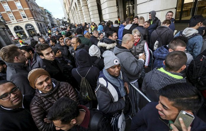 Customers queue outside an Apple store prior to the sale of the iPhone 6S in London