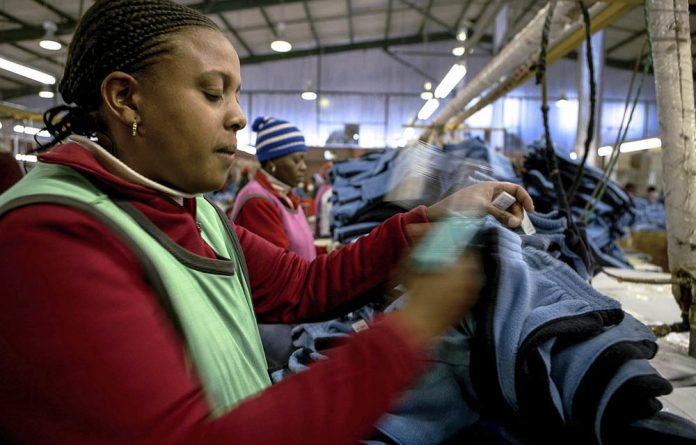 A local textile worker labels items in a clothing factory in Maseru.