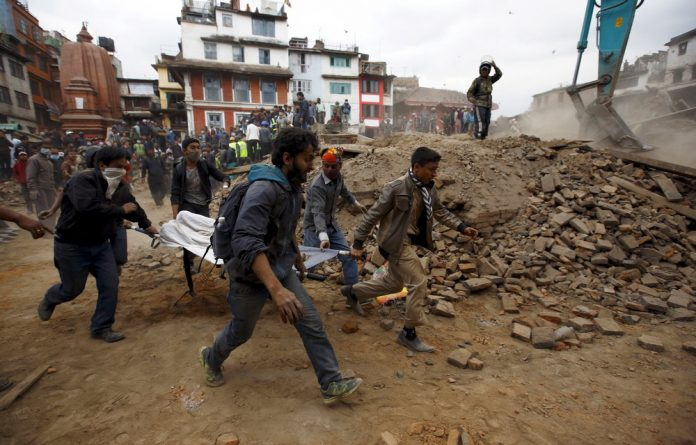 Rescuers carry the body of a victim who was stuck in the debris after the earthquake.