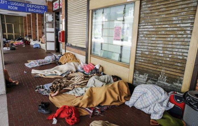 Dark days: Asylum seekers and the refugees at a railway station in Italy