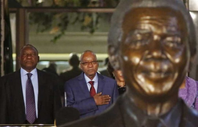 President Jacob Zuma and Deputy President Cyril Ramaphosa stand behind a statue of former President Nelson Mandela outside Parliament in Cape Town