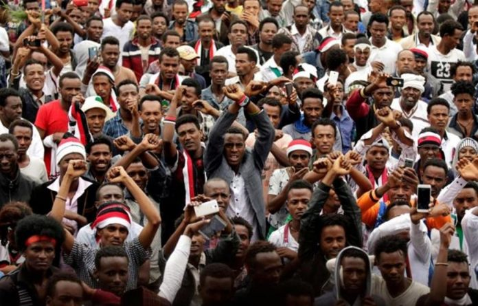 Demonstrators chant slogans while flashing the Oromo protest gesture