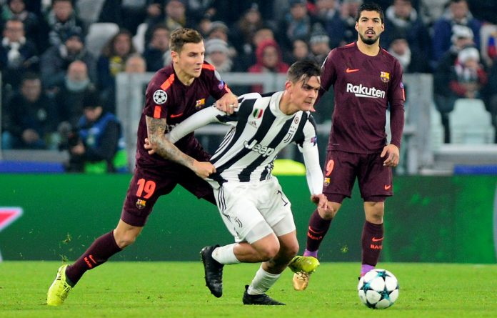 Juventus' Paulo Dybala in action with Barcelona's Lucas Digne.