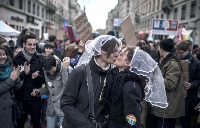 Two women wearing a wedding veil kiss each other during a demonstration to support same-sex marriages in Lyon