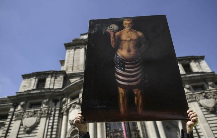 Satirical artist Kaya Mar poses with an artwork during a protest near the venue of the publication of the Iraq Inquiry report in London on July 6 2016.