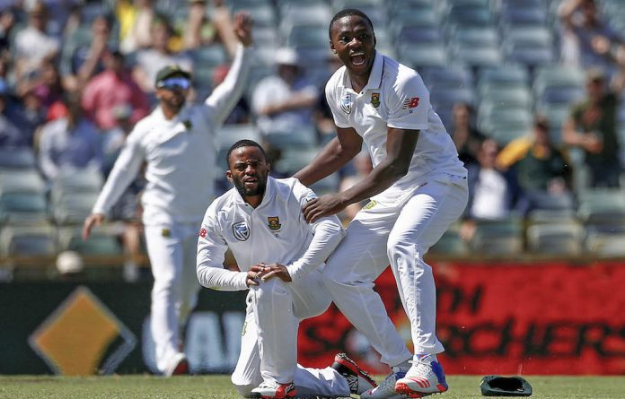 Men of the moment: First Test heroes Temba Bavuma and Kagiso Rabada appeal for the dismissal of Australia's David Warner after Rabada's stunning pick-up and throw.
