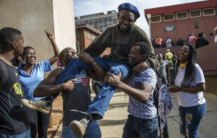Students from the University of the Witwatersrand give a hero's welcome to one of the protesters released from the Hillbrow police station.