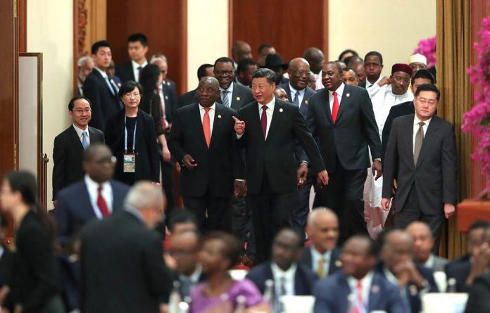 Scratch my back: China's President Xi Jinping walks with South African President Cyril Ramaphosa into the Focac round table conference in Beijing in September 2018. China's investment in Africa has risen dramatically.