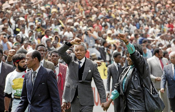 Sage warrior: Nelson and Winnie Mandela salute onlookers on entering the FNB Stadium in Soweto after his release in 1990