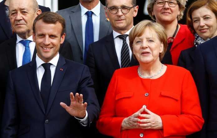 German Chancellor Angela Merkel and French President Emmanuel Macron pose for a family photo with the Franco-German Ministerial Council before a meeting in Meseberg